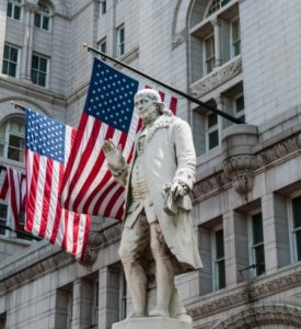 19654910 - benjamin franklin in front of american flags.
